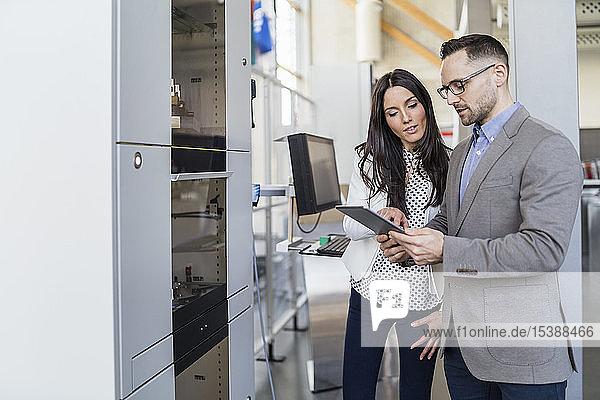 Geschäftsmann und Geschäftsfrau mit Gespräch in moderner Fabrik