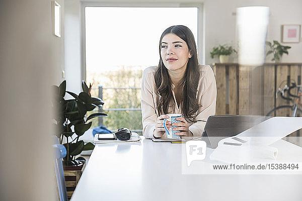 Young woman sitting at table at home thinking