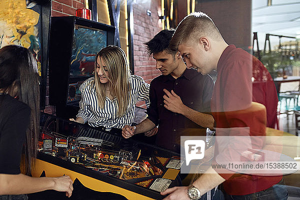 Man playing pinball watched by friends