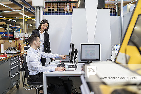 Geschäftsmann und Geschäftsfrau unterhalten sich am Computer in einer modernen Fabrik