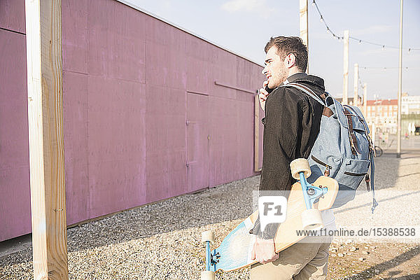 Young man with skatebaord and cell phone on the move in the city
