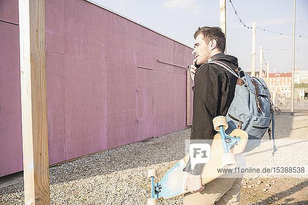 Junger Mann mit Skatebaord und Handy in der Stadt unterwegs