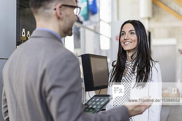 Geschäftsmann und lächelnde Geschäftsfrau im Gespräch in einer modernen Fabrik