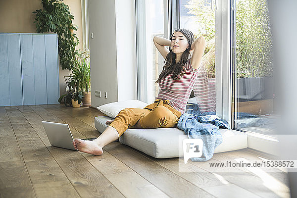 Relaxed young woman sitting at the window at home with laptop