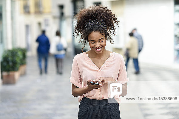 Smiling young woman using cell phone in the city