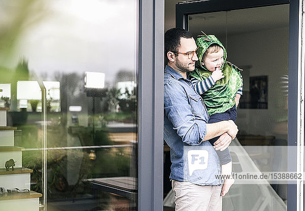 Father carrying son in a costume at terrace door at home