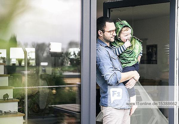 Vater trägt Sohn in einem Kostüm an Terrassentür zu Hause