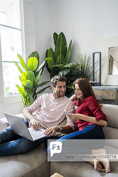 Mann und Frau sitzen auf der Couch  arbeiten am Laptop  benutzen ein Smartphone