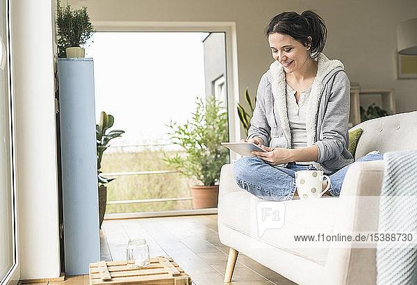 Frau mit Becher  die zu Hause auf der Couch sitzt und ein Tablett benutzt