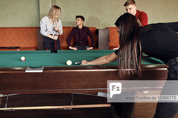 Young woman playing billiards with friends