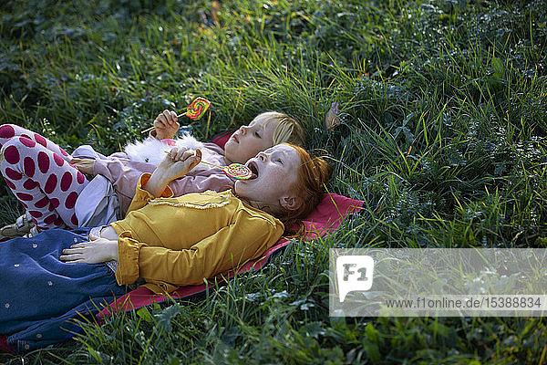 Two sisters lying in a field holding lollipops