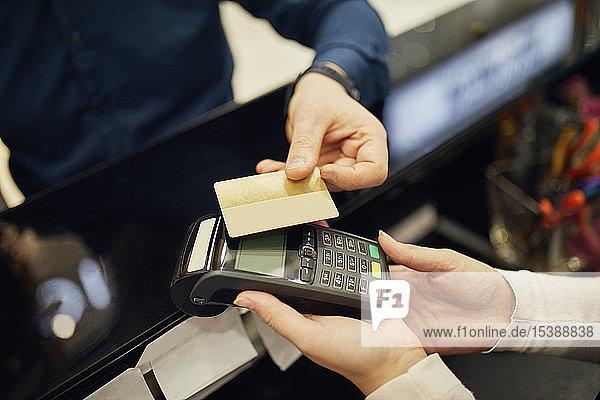 Nahaufnahme eines bargeldlos mit Kreditkarte zahlenden Kunden in einem Geschäft