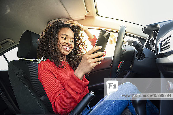 Happy young woman using cell phone in a car