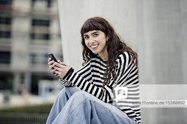 junge Frau  die ein gestreiftes Hemd trägt und ein Smartphone benutzt