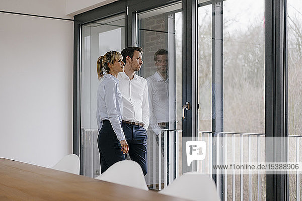 Erfolgreiche Geschäftsfrau und erfolgreicher Geschäftsmann im Konferenzraum  Blick aus dem Fenster