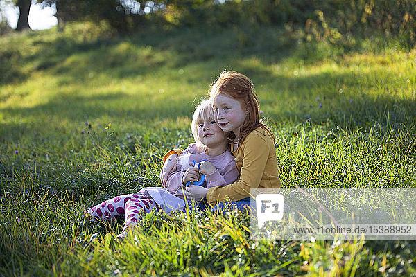 Two sisters cuddling in field