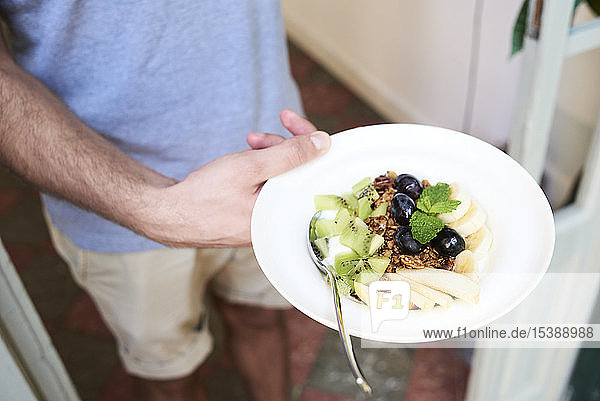 Close-up of man holding plate with healthy breakfast