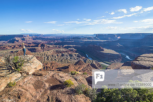USA  Utah  Woman at a overlook over the canyonlands and the Colorado river from the Dead Horse State Park