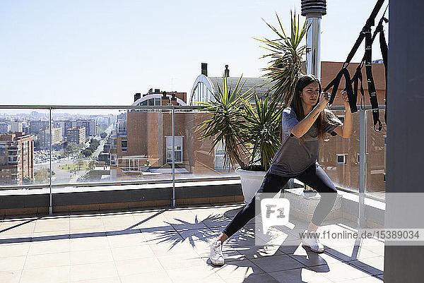 Sportliche junge Frau beim Suspensionstraining auf der Dachterrasse
