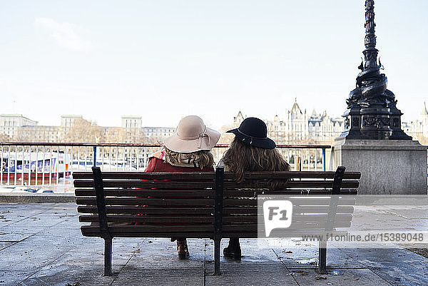 UK  London  rear view of two women sitting on a bench at River Thames promenade