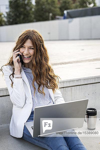 Junge Geschäftsfrau  die auf einer Treppe in der Stadt sitzt und mit Laptop und Smartphone arbeitet