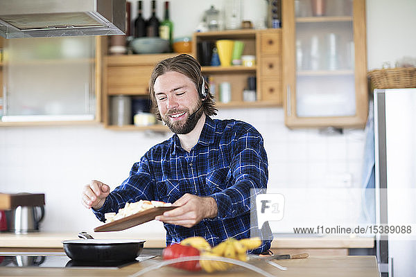 Young man with beard and plaid shirt  and headset cooking vegetables in kitchen