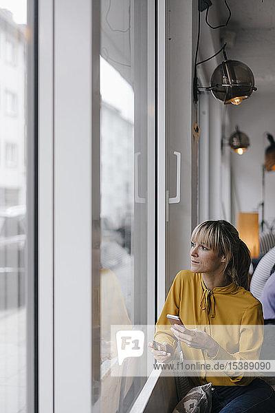 Blonde Geschäftsfrau sitzt am Fenster und bezahlt mit Smartphone und Kreditkarte