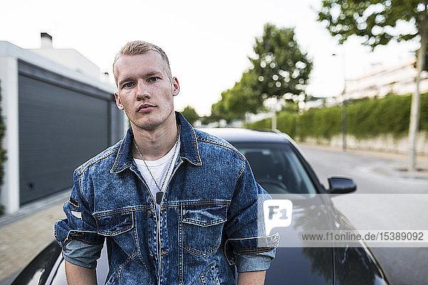 Porträt eines jungen Mannes in Jeansjacke  der vor einem Auto steht