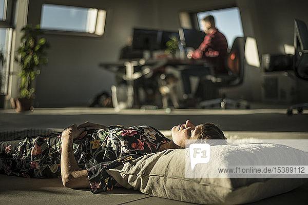 Frau macht ein Nickerchen  liegt auf einem Kissen auf dem Büroboden