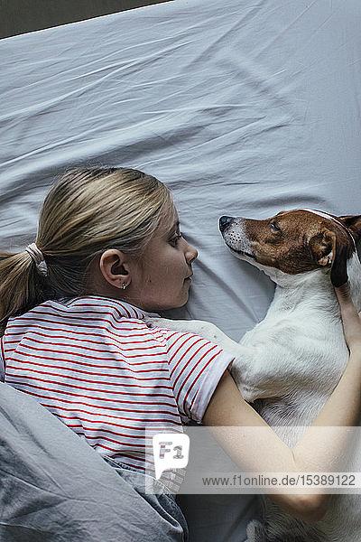 Blondes Mädchen liegt auf dem Bett und kuschelt mit ihrem Hund