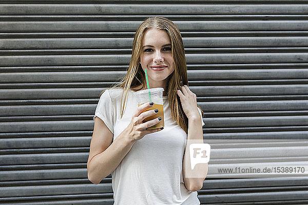 Junge Frau in der Stadt trinkt Kaffee zum Mitnehmen