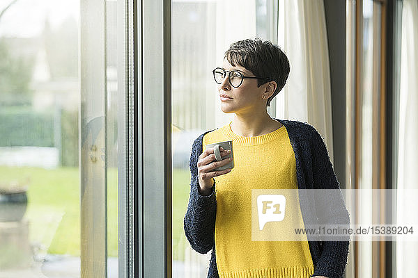 Portrait of woman with cup of coffee looking out of window