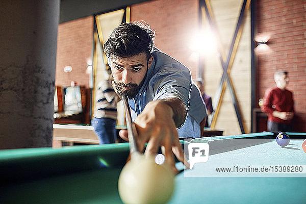 Porträt eines konzentrierten Mannes beim Billardspielen