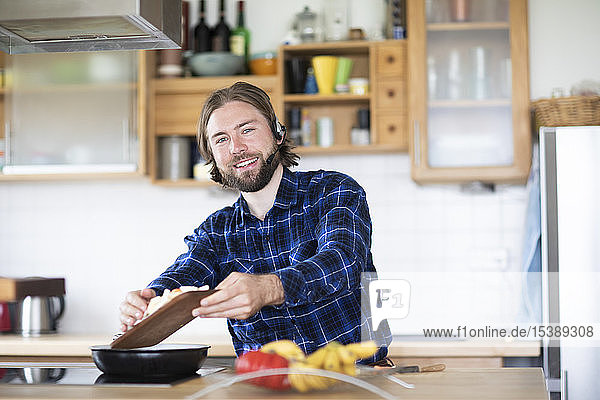 Junger Mann mit Bart und kariertem Hemd und Headset  der in der Küche Gemüse kocht