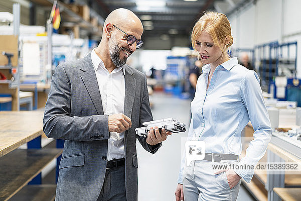Businessman and businesswoman examining workpiece in factory