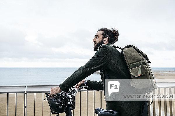 Mann mit E-Bike macht Pause an Strandpromenade