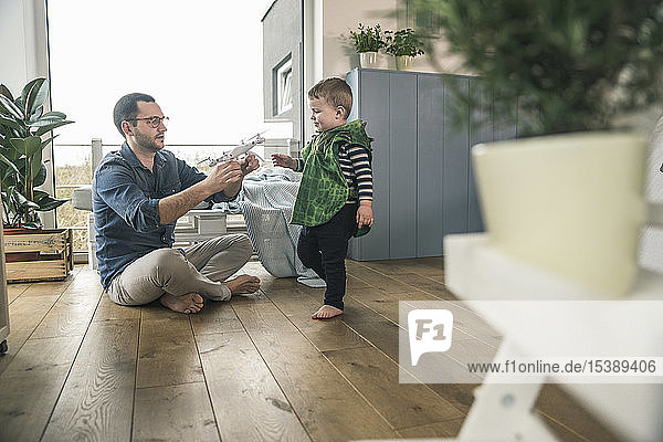 Boy in a costume and father playing with a drone at home