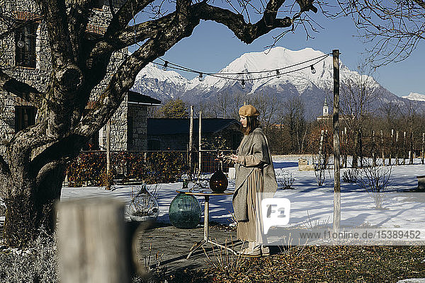 Italy  Limana  fashionable woman arranging twig in glass bottle outdoors