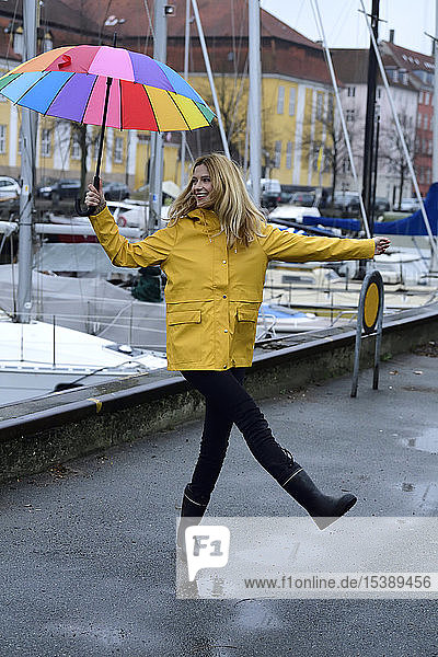 Denmark  Copenhagen  happy woman with colourful umbrella at city harbour