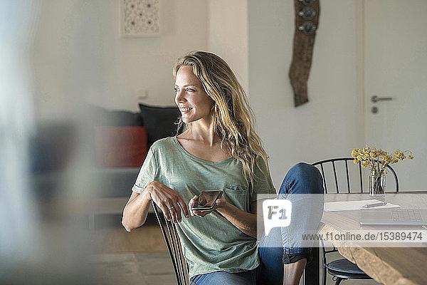 Lächelnde Frau mit Handy und Laptop auf dem Esstisch zu Hause