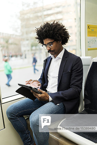 Spain  Barcelona  businessman in a tram using tablet