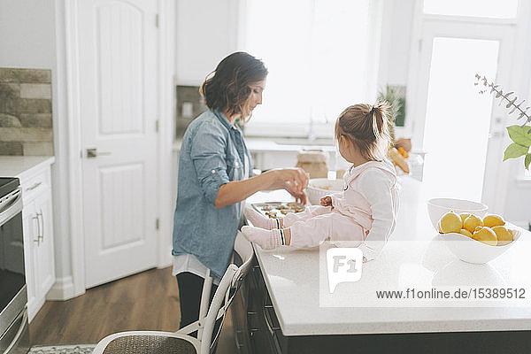 Mutter und Tochter backen gemeinsam einen Kuchen