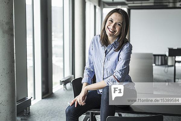 Porträt einer lächelnden Geschäftsfrau  die im Büro auf einem Konferenztisch sitzt