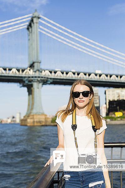Junge Frau erkundet New York City,  steht mit Kamera an der Brooklyn Bridge