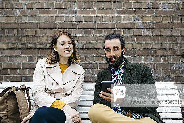 Couple sitting on a bench at a brick wall sharing cell phone