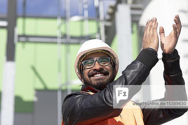 Porträt eines glücklichen Bauingenieurs vor dem Kraftwerk mit Schutzhelm und Sicherheitsweste klatschend in die Hände