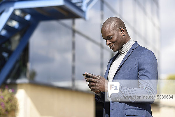 Smiling businessman wearing blue suit and grey turtleneck pullover looking at cell phone