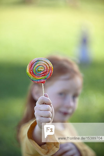Girl holding a colourful lollipop
