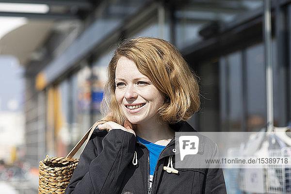 Porträt einer lächelnden Frau mit Einkaufstasche vor einem Supermarkt