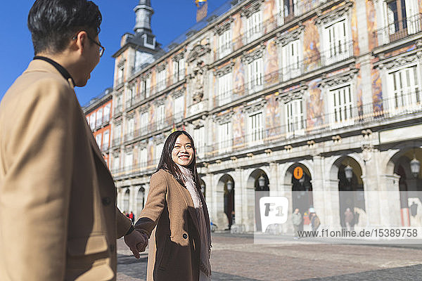 Spain  Madrid  happy young tourist couple holding hands on Plaza Mayor